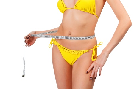 weight control: Beautiful woman measuring her waist, isolated on white background  Stock Photo