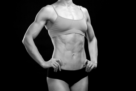 fat burning: Female fitness bodybuilder posing against black background