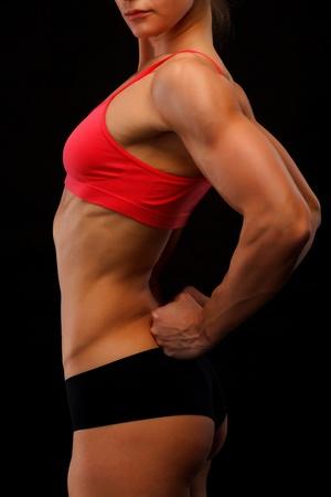 back exercise: Female fitness bodybuilder posing against black background