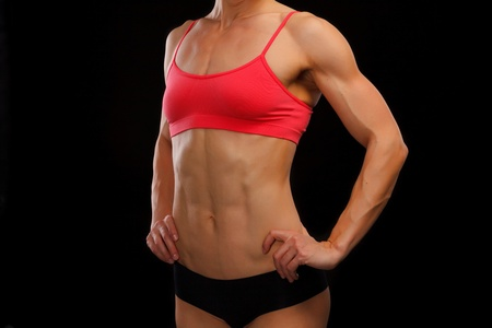 Muscular female body against black background Stock Photo - 12501030