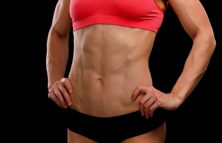 tanned woman: Muscular female body against black background