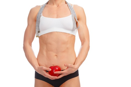 Muscular woman with apple and tape measure posing against white background  photo