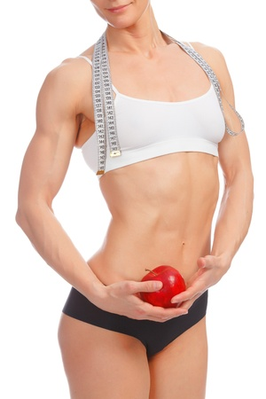 muscular build: Muscular woman with apple and tape measure posing against white background  Stock Photo