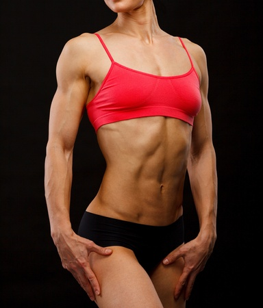 female bodybuilder: Muscular female body against black background.