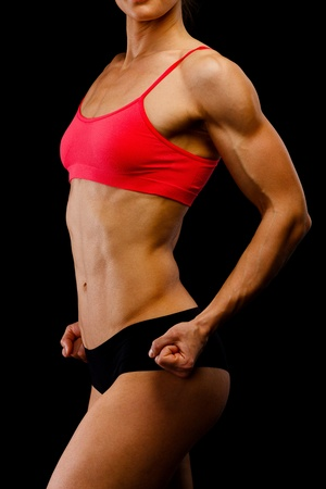 Muscular female body against black background. photo