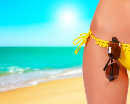 tanned body: Closeup of a female body in a swimsuit with sunglasses. A day at a beach concept Stock Photo