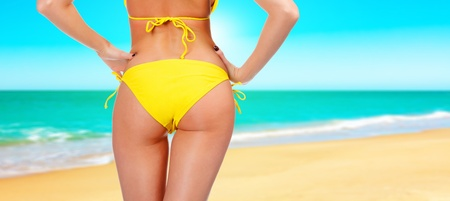 Gros plan d'un backside femme en maillot de bain jaune. Une journ�e � la plage un concept photo
