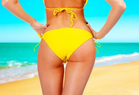 hintern: Nahaufnahme eines weiblichen Hintern in einem gelben Badeanzug. Ein Tag am Strand ein Konzept.