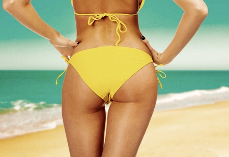 Closeup of a female backside in a yellow swimsuit  Old film colors  A day at a beach concept   photo