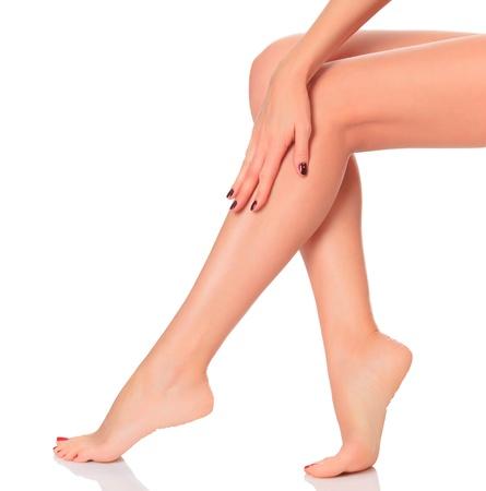 benen: Goed verzorgde vrouwelijke benen na het ontharen procedure. Een dag in een kuuroord concept. Geà ¯ soleerd op een witte achtergrond.