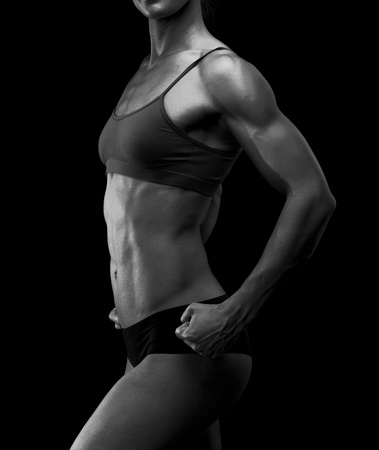 weight training: Black and white image of a muscular female body against black background.