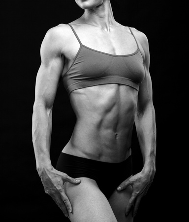 abdominal: Black and white image of a muscular female body against black background.