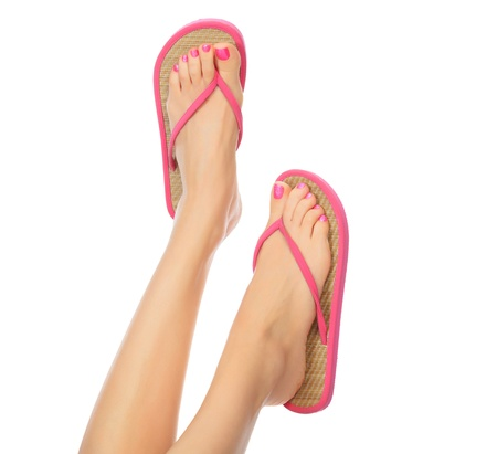 Funny pink sandals on female feet. Isolated on white background photo