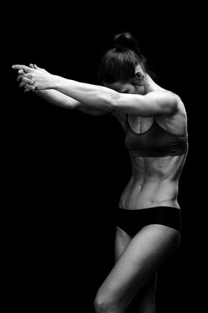 female bodybuilder: Black and white image of a muscular female body against black background.