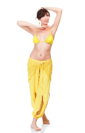 Belly dancer in yellow costume posing against white background photo