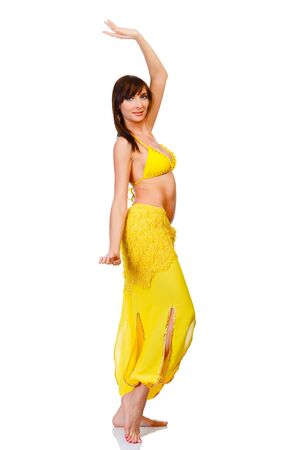 Belly dancer in yellow costume posing against white background Stock Photo - 12790862