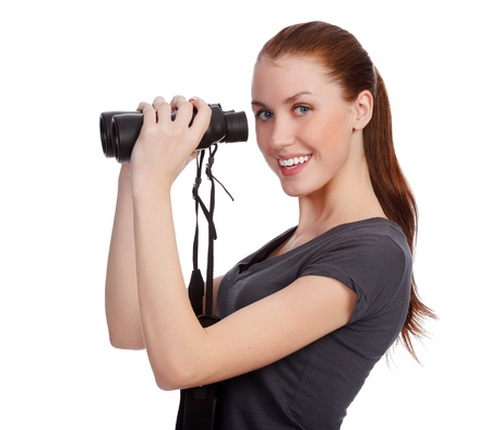 Smiling girl with binoculars posing against white background photo