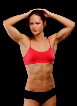 tricep: Female athlete posing against black background