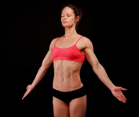 abdominal muscles: Female athlete posing against black background