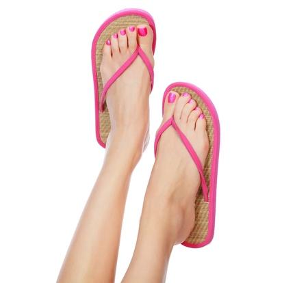 sandalia: Humor sandalias de color rosa en los pies femeninos. Aislado sobre fondo blanco. Foto de archivo