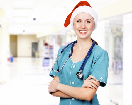 Smiling female medical doctor wearing red hat in a hall of a hospital. Christmas time concept Stock Photo