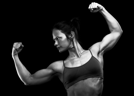 Female athlete posing against black background photo