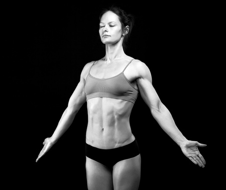 creative strength: Black and white image of female athlete posing against black background