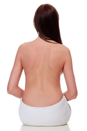 nude back: female torso against white background