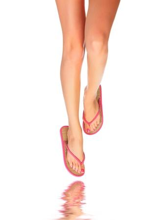 sandalia: Piernas femeninas con flip-flops, aisladas sobre fondo blanco. Foto de archivo