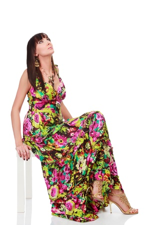 Woman in a bright summer dress posing against white background