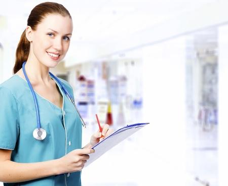 Glimlachende vrouwelijke arts met klembord in een gang van een ziekenhuis Stockfoto