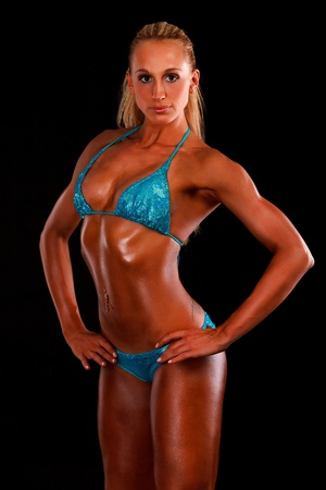 female muscle: muscular sexy woman posing against black background.