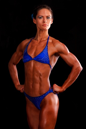 muscular woman posing against black background.  photo