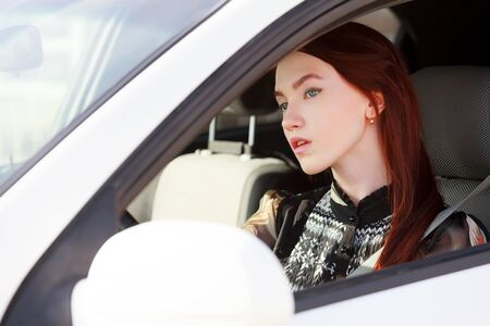 woman driving car: Pretty teenage girl in a car