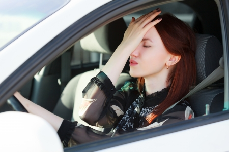 emotional stress: Troubles on the road, Girl hides face in hands while in a car