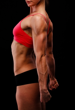 tricep: Muscular strong woman posing against a black background Stock Photo