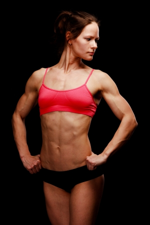female bodybuilder: Muscular strong woman posing against a black background Stock Photo
