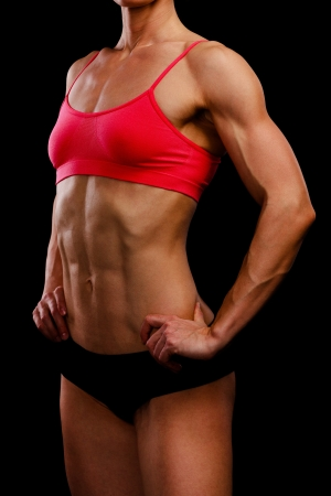 bodybuilder training: Muscular strong woman posing against a black background Stock Photo