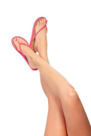 jolie pieds: Femme jambes avec des tongs, isolé sur fond blanc.