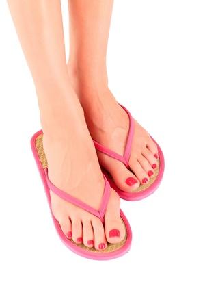 sandal: Piernas femeninas con flip-flops, aisladas sobre fondo blanco. Foto de archivo
