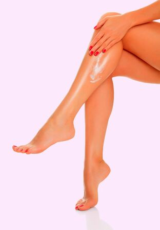 dishy: Woman applying cream to her tanned legs on a pink background