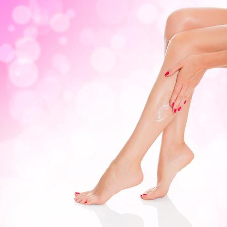 dishy: Woman applying cream to her legs  Stock Photo