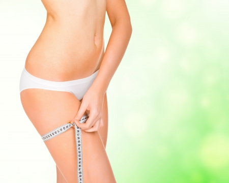 Young tanned woman measuring her body, green blurred background photo