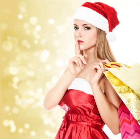 Female Santa with shopping bags posing against gold blurred background photo