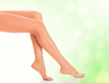 female feet: Perfect female legs on green blurred background Stock Photo