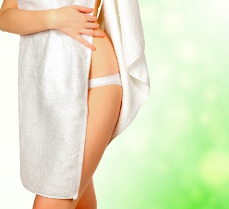 Woman wrapped in a white towel, green blurred background photo
