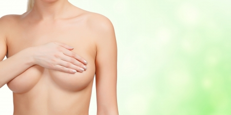 skin cancer: Female controlling breast for cancer, green blurred background
