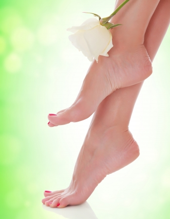 long feet: Female feet with a flower on green blurred background