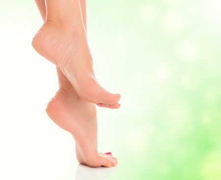 female feet on blurred green background  photo