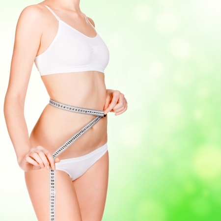 vientre femenino: joven de tomar mediciones de su cuerpo, fondo borroso verde.